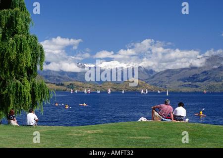 Picnickers watch the sailboats kakyaks on LAKE WANAKA on a beautiful summer afternoon SOUTH ISLAND NEW ZEALAND - Stock Photo