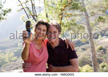 Couple taking picture of themselves with camera phone - Stock Photo