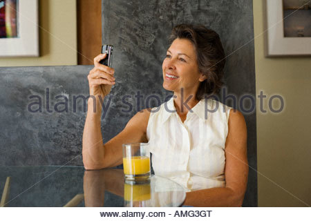 Woman sitting at a table with orange juice and a mobile phone - Stock Photo