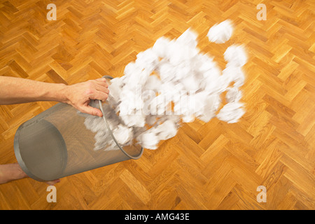 frustrated man throwing basket of waste paper across office in anger ideas scrunched up into balls of trash - Stock Photo