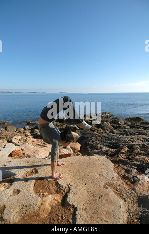Mixed race young woman half asian half spanish exercising oudoors and doing a handstand in Ibiza Spain - Stock Photo