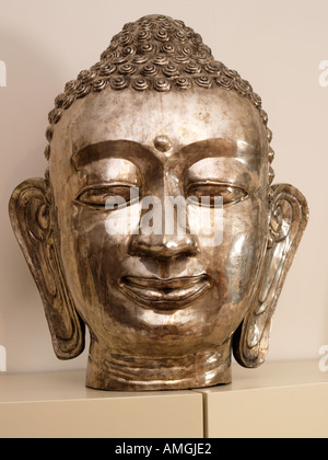 Shiny metal hindu indian god deity head with big ears standing on a cabinet in a room - Stock Photo