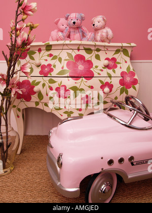 Children little girls room decoration ideas with flowers teddy bears painted furniture and pink toy car - Stock Photo