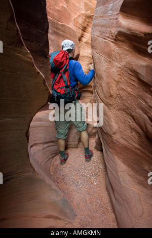 Hiker in Peek a Boo slot canyon near Escalante in Grand Staircase National Monument Utah USA - Stock Photo