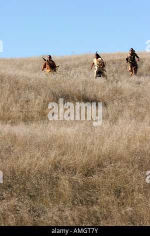 Three Native American Indian men running in the dead grasses - Stock Photo