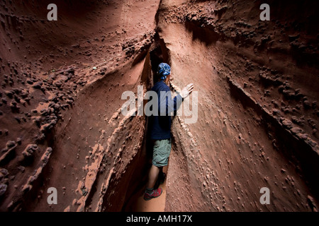 Man hiker in sandstone narrows of Spooky Gulch near Escalante in Grand Staircase National Monument Utah USA - Stock Photo