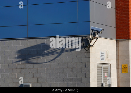 Security camera casting a long shadow, mounted on side of building. - Stock Photo