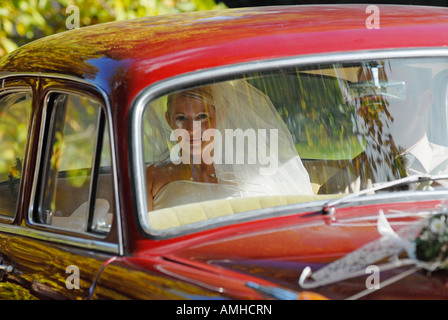Bride in the wedding car on the way to church - Stock Photo