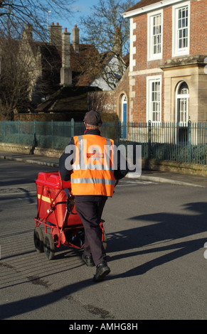 Postman Pushing his Red Trolley Containing Mail on his Delivery Round in Salisbury Wiltshire England UK - Stock Photo