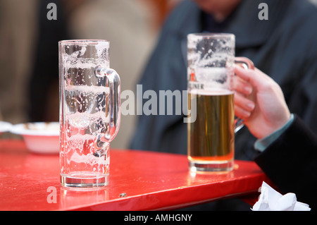 empty german beer glass sitting on a red outdoor cafe table next to womans hand holding half full glass Berlin Germany - Stock Photo