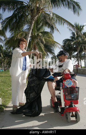 Miami Beach Florida Lummus Park Coastal Cleanup Day volunteer disabled man woman litter bag electric scooter - Stock Photo