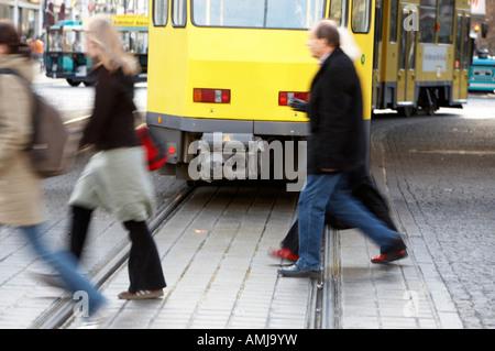 people walking across tramlines behind moving BVG berlin yellow tram travelling though alexanderplatz Berlin Germany - Stock Photo