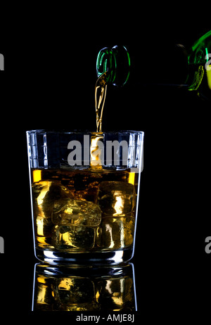 Whiskey being poured into a glass of ice against a black background - Stock Photo