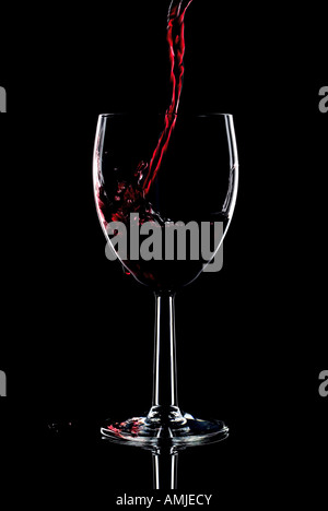 Red wine being poured into a glass and splashing over the side Low key black background Stock Photo