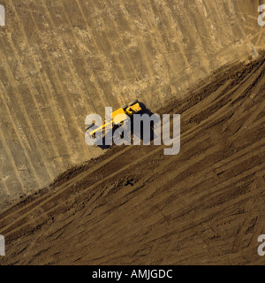 Tractor on landfill site overhead aerial view - Stock Photo