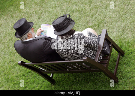 Man and woman sitting on a bench at Royal Ascot horse race, York, Great Britain - Stock Photo