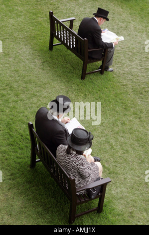 People sitting on benches at Royal Ascot horse race, York, Great Britain - Stock Photo