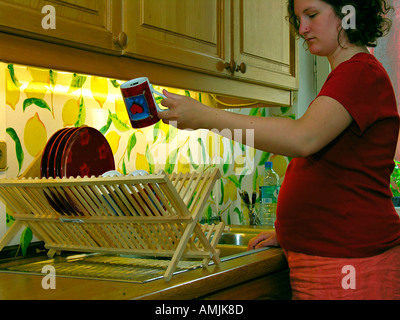 MR PR pregnant woman washing the dishes in the kitchen - Stock Photo