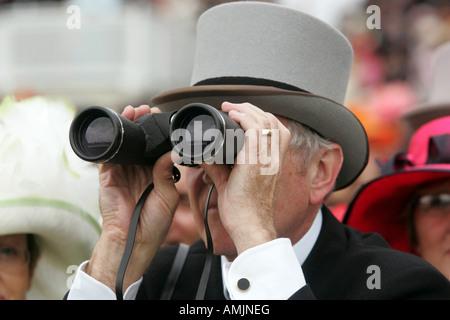 Man looking through binoculars at Royal Ascot horse race, York, Great Britain - Stock Photo
