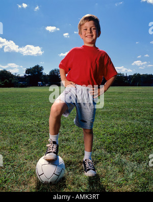 Young Boy standing with his foot on a soccer ball - Stock Photo
