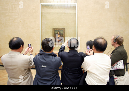 Tourists taking pictures of the Mona Lisa at the Louvre Museum, Paris, France - Stock Photo