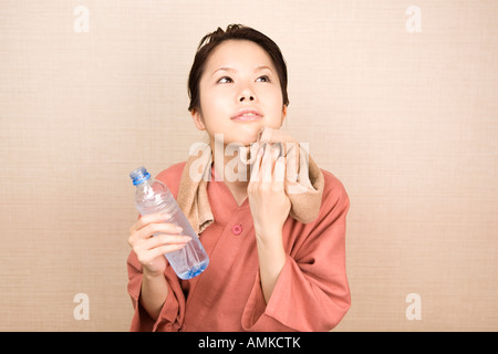 Young woman wiping face with towel - Stock Photo