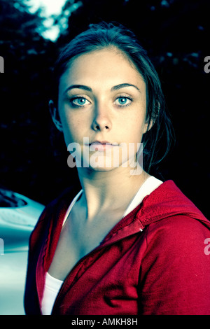 Head and shoulders portrait of a young woman wearing a red jacket - Stock Photo