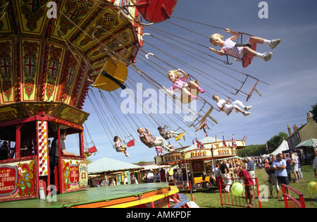 Two girls ride in seats on a carousel. Findon Village Sheep Fair, West Sussex England