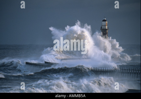 Wave breaks over the Lighthouse on Roker Pier in Sunderland, England, UK, during a winter storm - Stock Photo