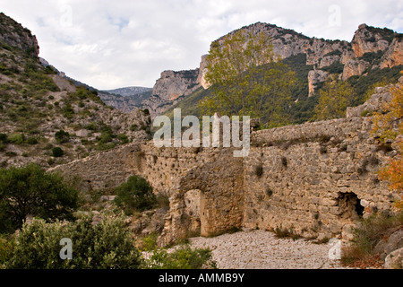Ruins of mediaeval fortifications above the village of St Guilhem le Desert - Stock Photo