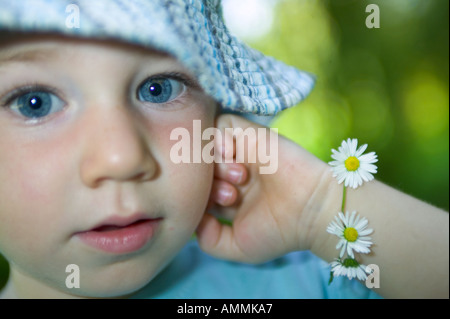 Young child with daisy chain around his wrist looking into camera with blue eyes - Stock Photo