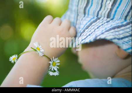 Young child with daisy chain around his wrist holding hat - Stock Photo