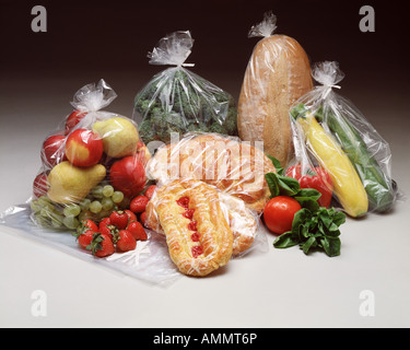 clear plastic storage bags w food fruit vegetables bread pastry grocery items fresh grapes - Stock Photo