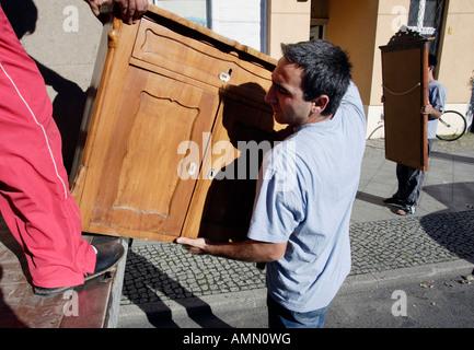 Removal men unloading furniture, Berlin, Germany - Stock Photo