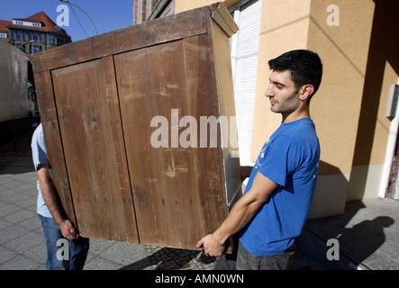 Removal men carrying furniture, Berlin, Germany - Stock Photo