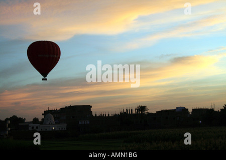 Hot Air Balloon Silhouetted in Front of Beautiful Sunrise [Near Luxor, Egypt, Arab States, Africa].             - Stock Photo
