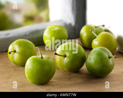Organic fresh picked Greengage plum in a rustic kitchen - Stock Photo