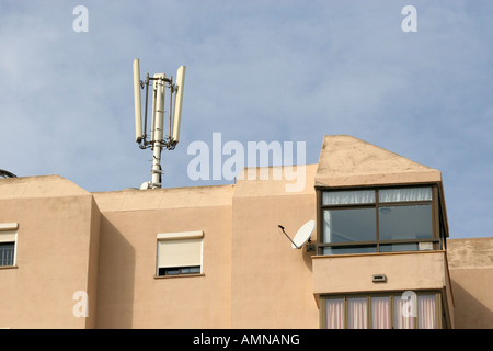 Mobile phone mast positioned on top of block of flats close to the sea in Palma Nova. - Stock Photo