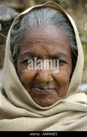 Portrait of an old lady with a pierced nose in the hood near Pokhara Nepal - Stock Photo