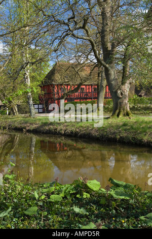 Traditional village cottage in front of a pond. The Funen Village. Odense. Denmark, - Stock Photo