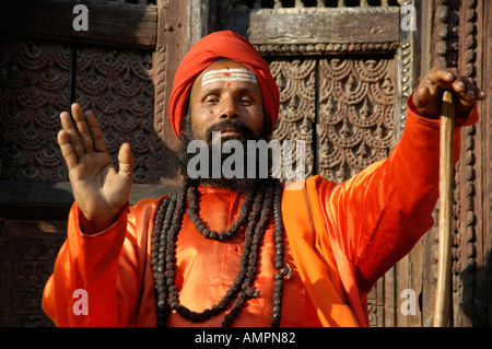 Holy man sadhu with many necklesses dressed in shining orange robe Kathmandu Nepal - Stock Photo