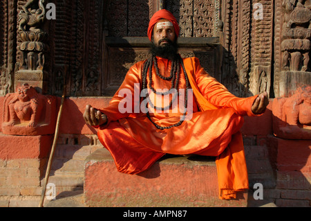 Holy man sadhu with many necklesses dressed in shining orange robe is sitting in front of a temple Kathmandu Nepal - Stock Photo