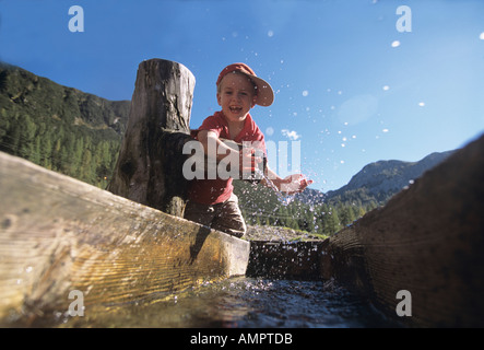 Boy sitting on tree trunk - Stock Photo