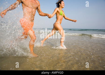 Couple Running and Splashing About at the Beach - Stock Photo
