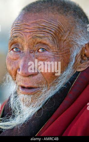 Elderly pilgrim lama outside Palcho Monastery Gyantse Tibet - Stock Photo