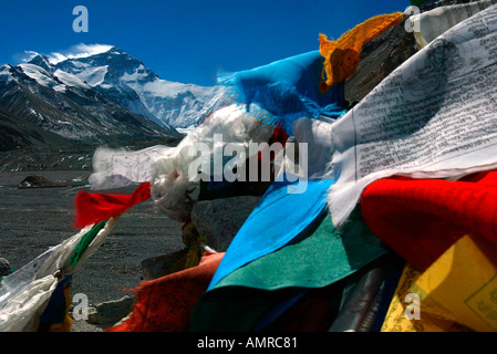 Prayer flags flutter on a base camp cairn in front of Mount Everest north face Himalayas Tibet - Stock Photo