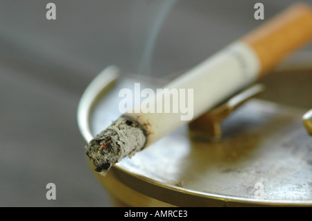 Burning cigarette in ashtray, close-up - Stock Photo