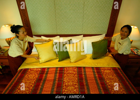 Housemaids arranging pillows cushion on suite bed J W Marriott Phuket Resort and Spa Thailand - Stock Photo