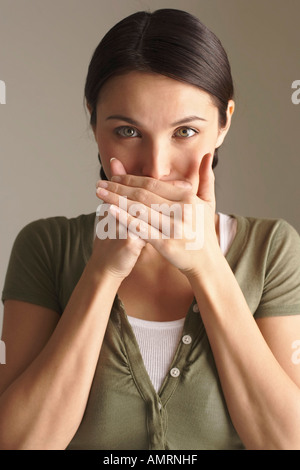 Woman Covering Mouth with Hands - Stock Photo