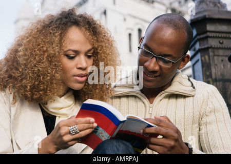 African couple looking at guide book - Stock Photo